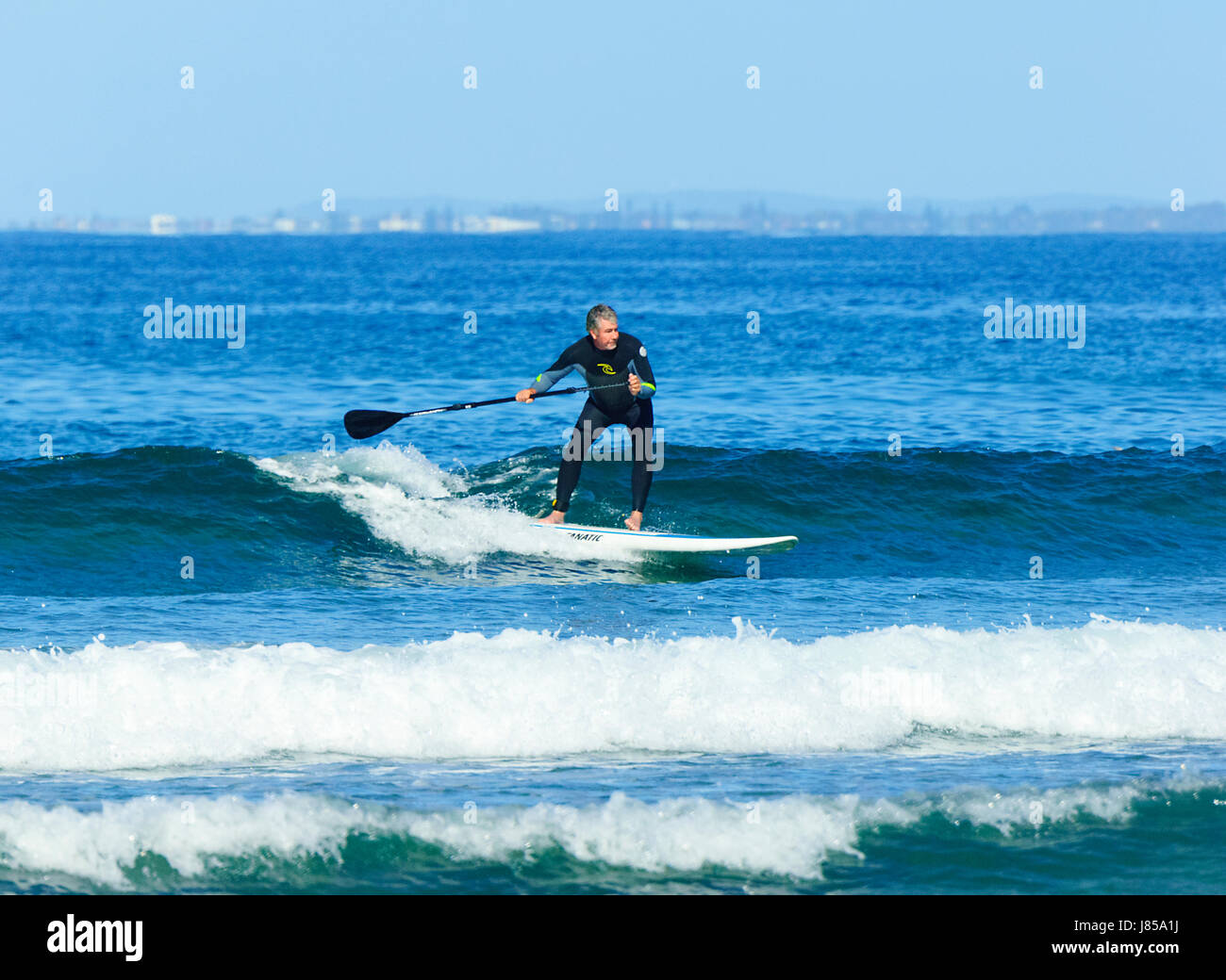 Man 50-60 surfing on a stand up paddleboard and wearing a wetsuit, 7 Mile Beach, Gerroa, New South Wales, NSW, Australia - Stock Image