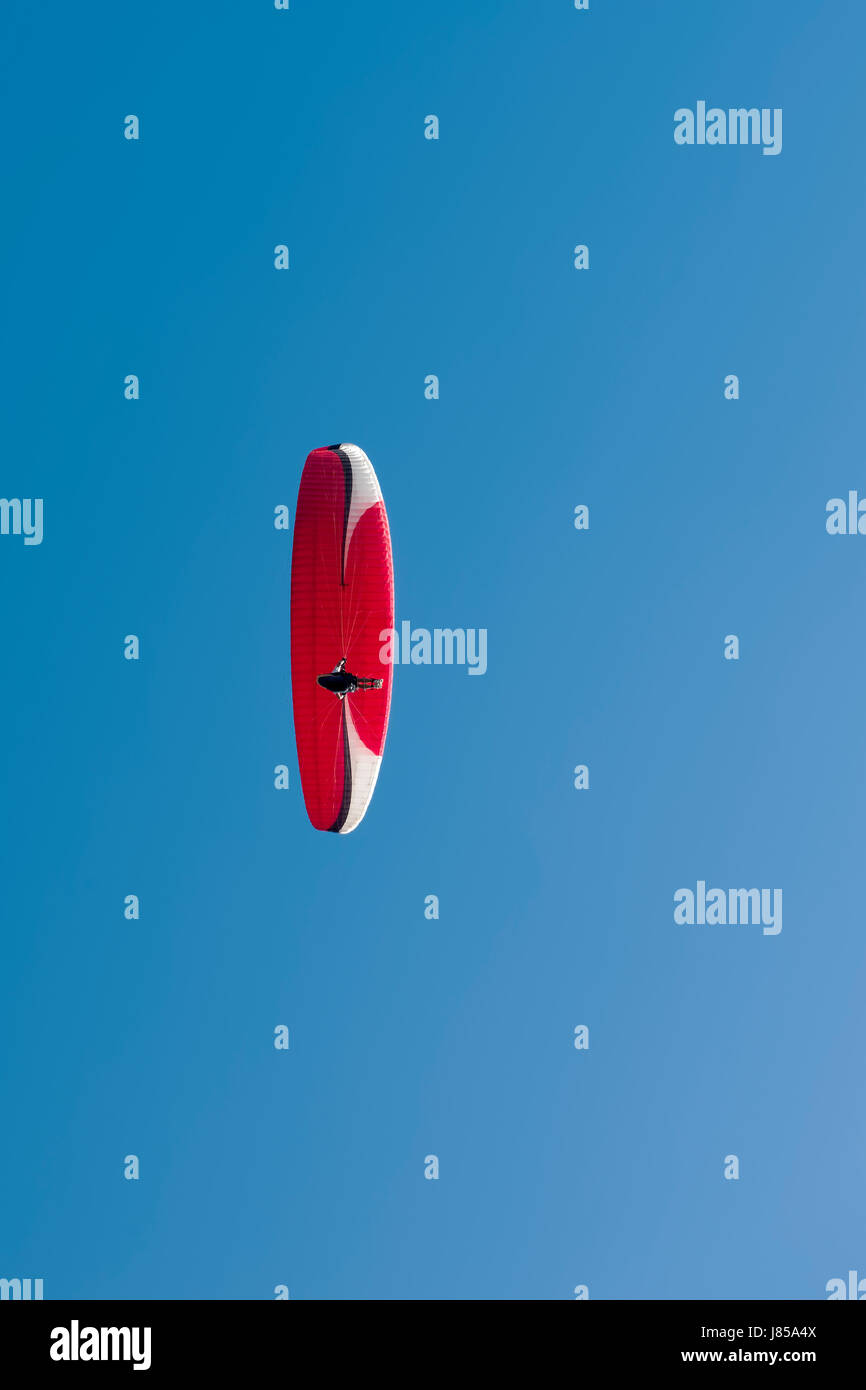 Colorful hang glider in sky over blue. - Stock Image