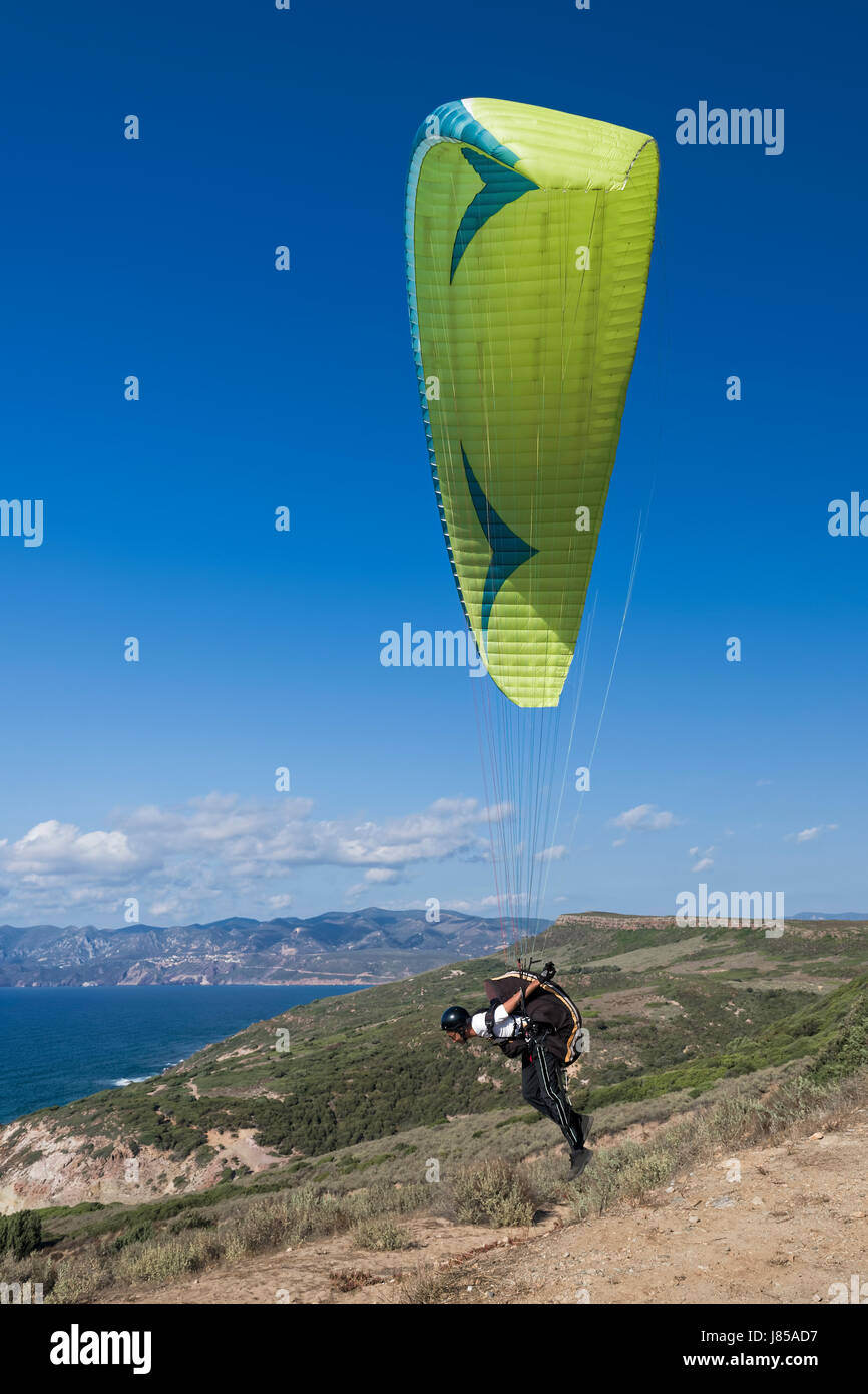 Colorful hang glider in sky over blue sea Stock Photo