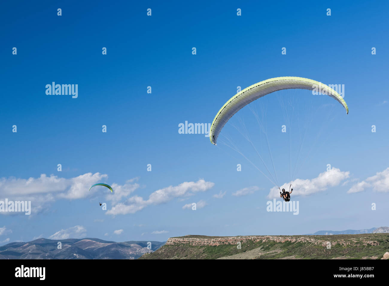 Colorful hang glider in sky over blue - Stock Image