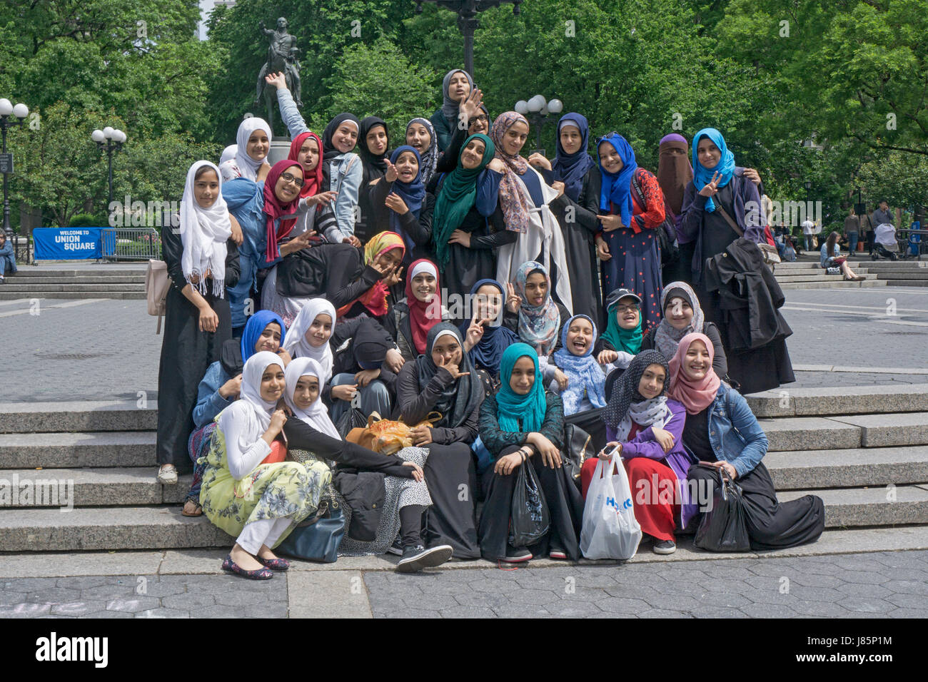 A group of religious Muslim females classmates in hijabs pose for a class photo in Union Square Park in Manhattan, - Stock Image