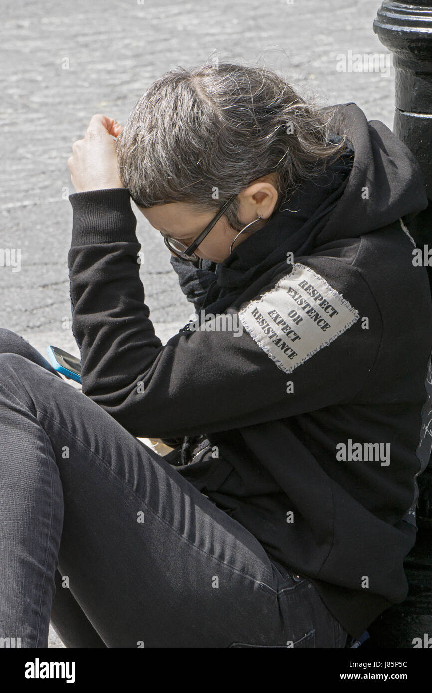 A woman in Union Square with an anti-Trump patch on her jacket reading, 'Respect Existence or Expect Resistence.' - Stock Image