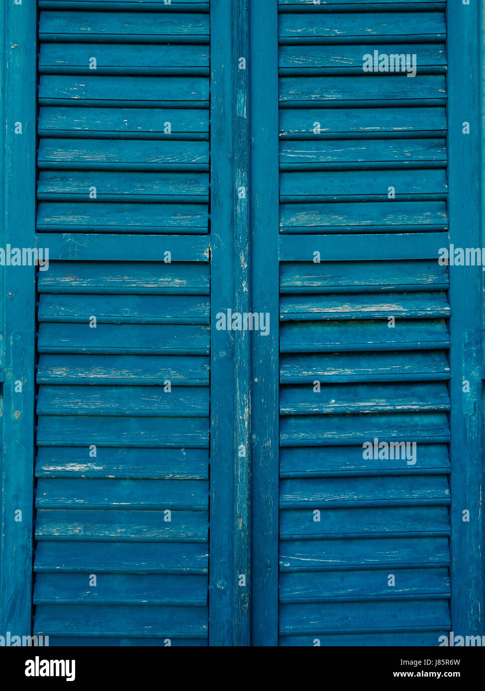 Wooden window shutters in blue. Antique homemade shutters on the windows.