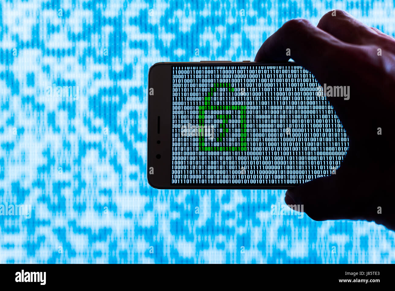 Hand holding a smartphone with a locker unlocked against binary code on screen - Stock Image