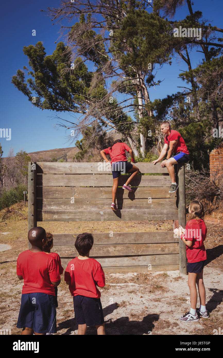 Trainer assisting kids to climb a wooden wall during obstacle course training at boot camp - Stock Image