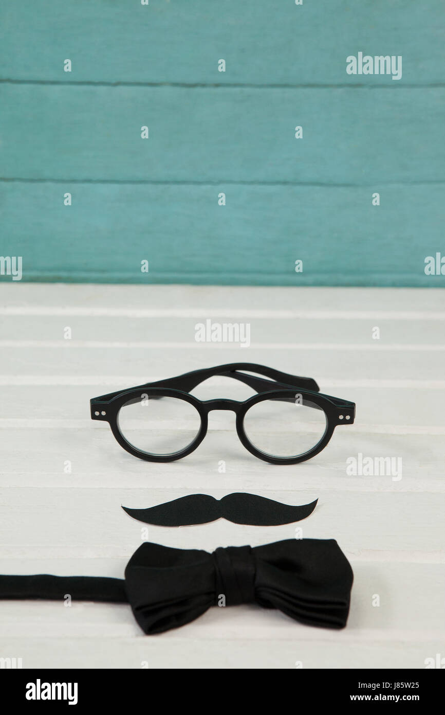 High angle view of eyeglasses with mustache and bowtie on wooden table - Stock Image