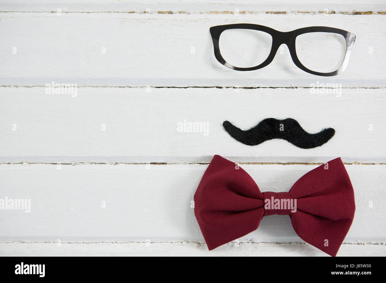 Close up of eyeglasses and bow tie arranged with mustache on wooden table - Stock Image