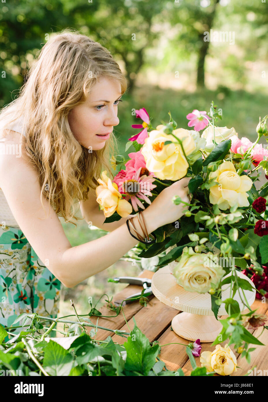 celebration, wedding, flora, beauty of nature concept - blond blue-eyed young woman arranges flower composition - Stock Image