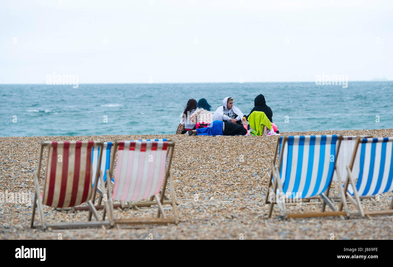 Brighton, UK. 27th May, 2017. What a difference a day makes as visitors huddle up on Brighton beach as the temperature - Stock Image