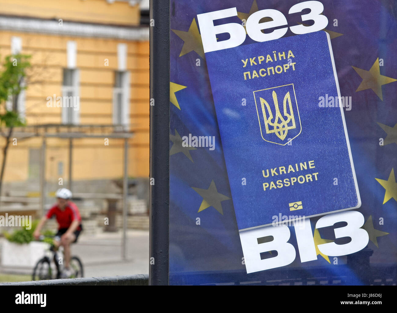 May 27, 2017 - Kiev, Ukraine - A cyclist rides near a banner with image of Ukrainian passport on the background Stock Photo