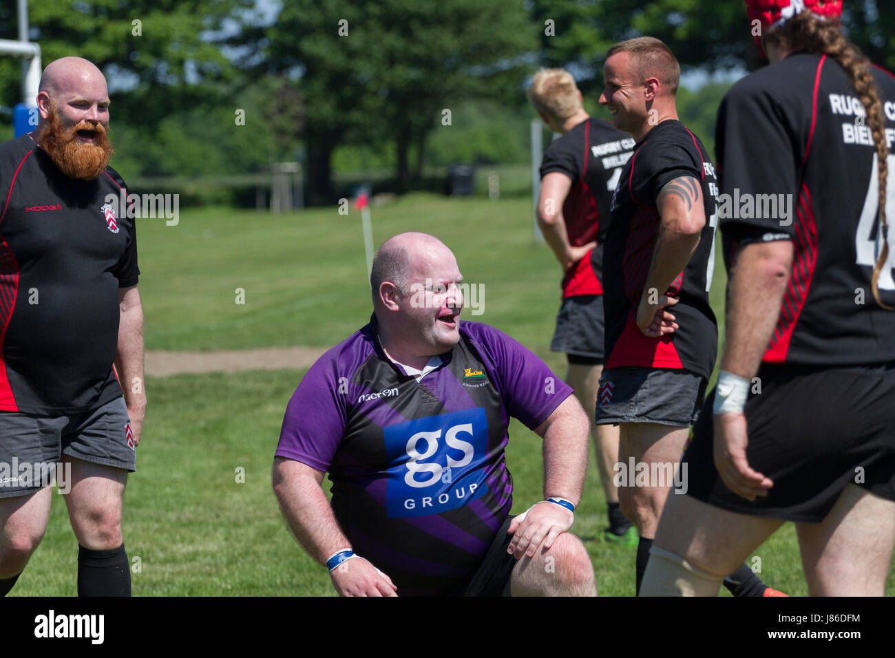 Humorous and good-natured moment in friendly rugby match - Stock Image
