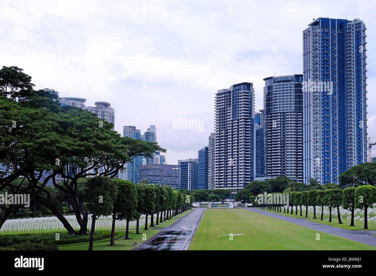 View of modern buildings across the Manila American Cemetery and Memorial which has the largest number of graves Stock Photo
