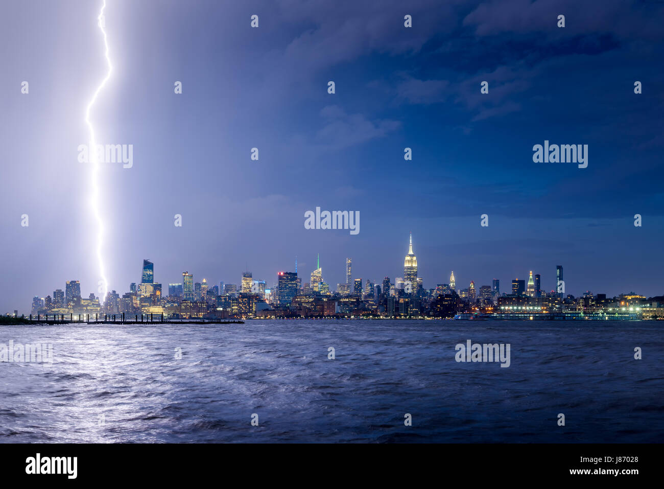 Lightning striking Midtown New York City skyscrapers at night. Stormy skies over Manhattan from the Hudson River - Stock Image