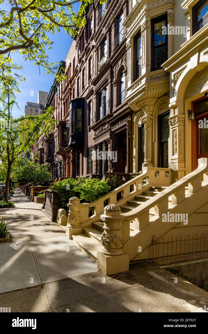 Row of brownstones with doorsteps and ornament in morning light. Upper West Side Street, Manhattan, New York City - Stock Image