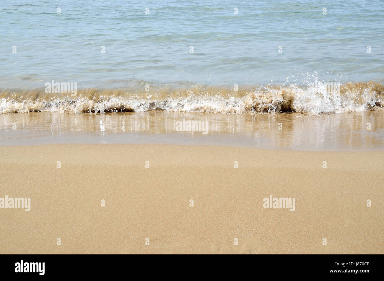 Waves of sea in a beach with fine sand - Stock Image