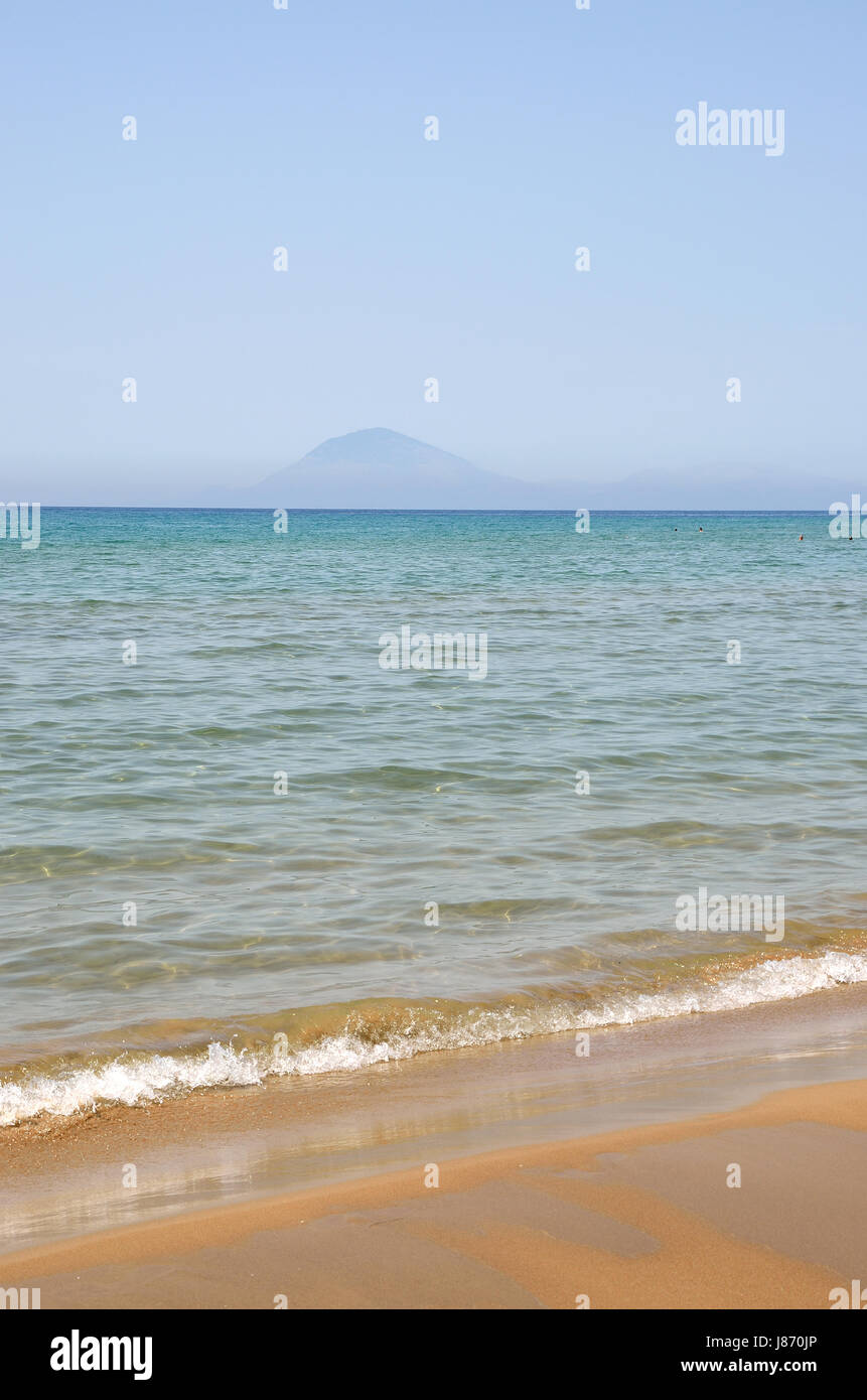 Sand ,sea , sky  and  silhouette of a mountain as background - Stock Image