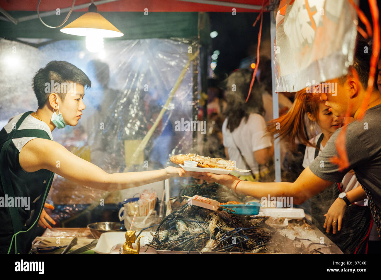 CHIANG MAI, THAILAND - AUGUST 27: Food vendor cooks and sells fish and seafood at the Saturday Night Market (Walking - Stock Image
