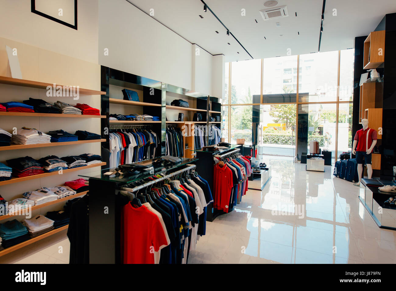 2a2a2aeb2b1 Interior of a clothing store. Clothing for men and women on the store  shelves. Shopping hall end clothing store.