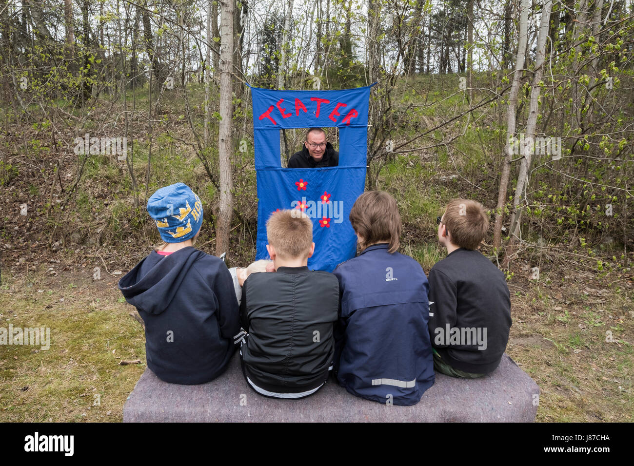 Child watching an outdoor theater, Upplands Väsby, Sweden. - Stock Image