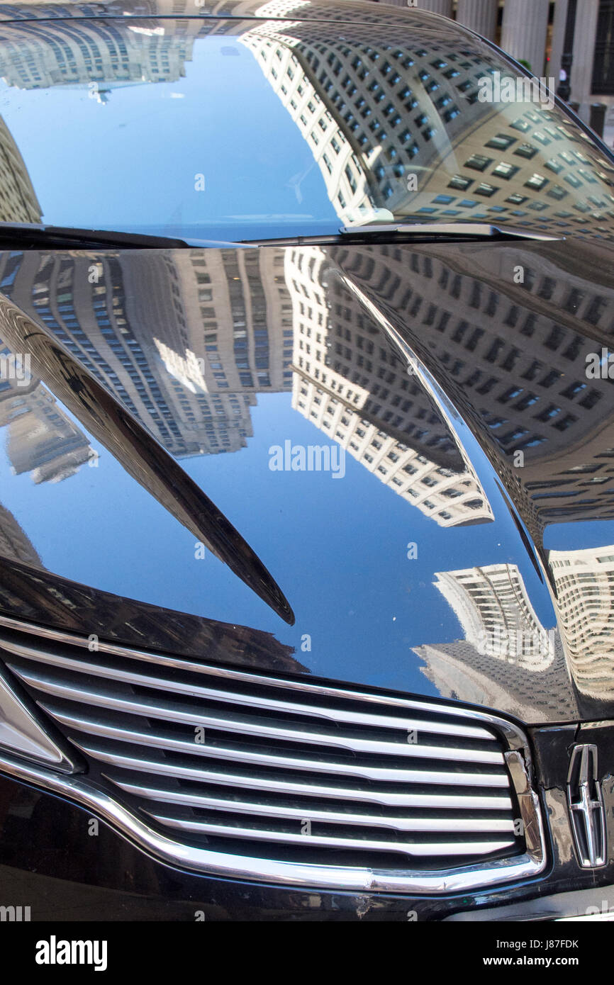 Reflected in the Lincoln limousine parked on LaSalle Street are the Chicago Board of Trade and other major financial - Stock Image