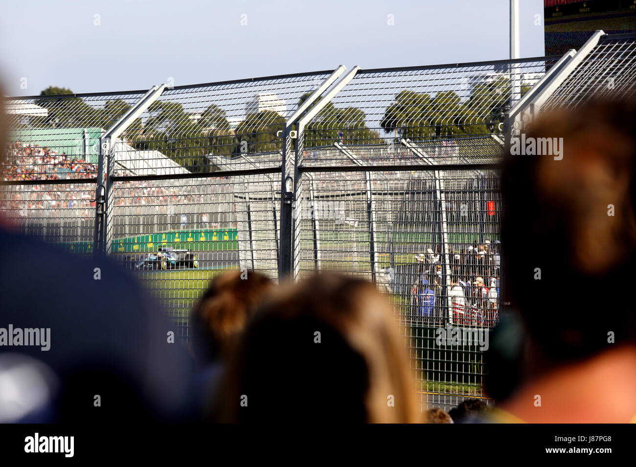 A fleeting glimpse of Lewis Hamilton through the heads of F1 fans. Please see description. - Stock Image