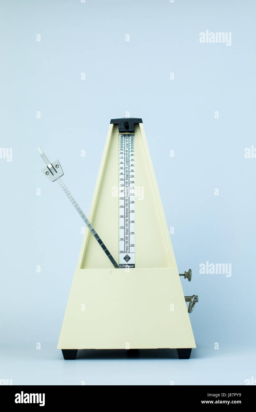 Classic Yellow Metronome in White Isolated Background - Stock Image