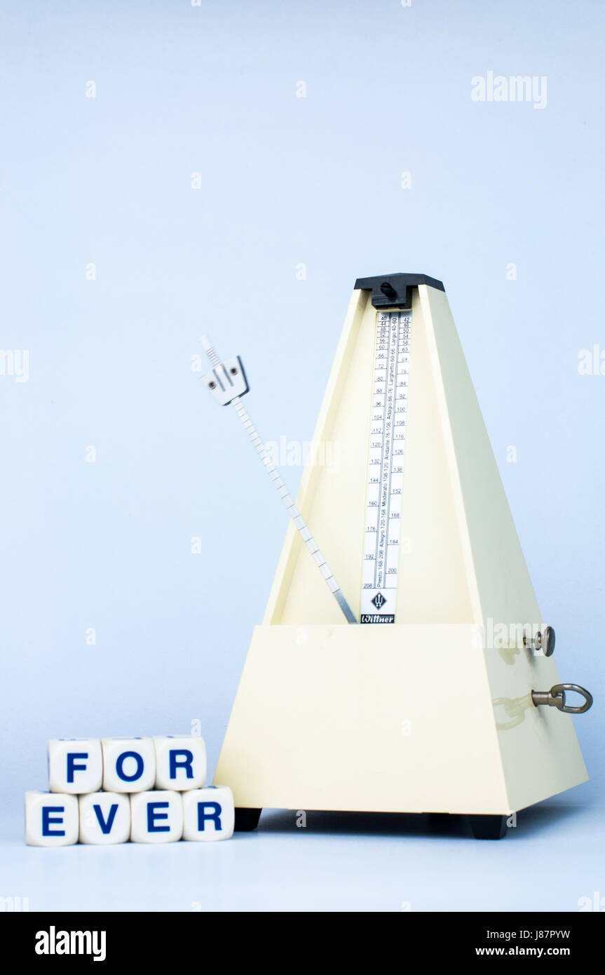 Classic Yellow Metronome with Alphabet Blocks say FOREVER in White Isolated Background - Stock Image