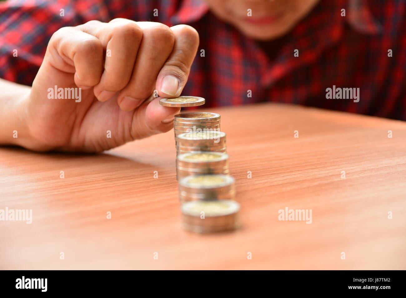 Saving money concept and hand putting money coin stack growing for business - Stock Image