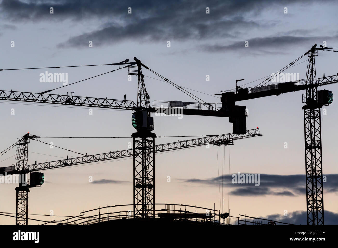 View of construction cranes on construction of an apartment house site with silhouetted over amazing abstract sunrise - Stock Image