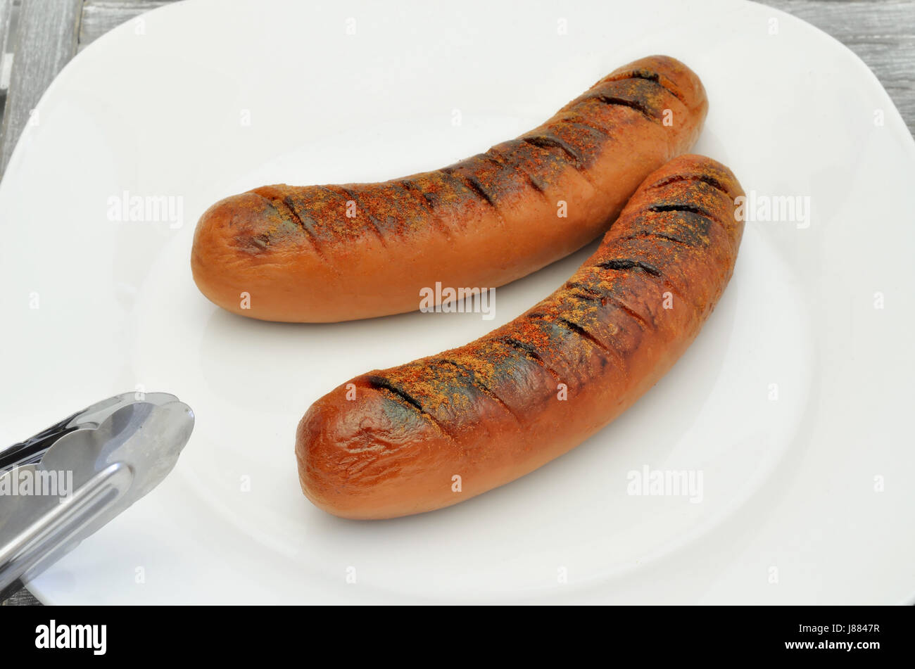 two grilled sausages on white plate, close up, macro, full frame Stock Photo