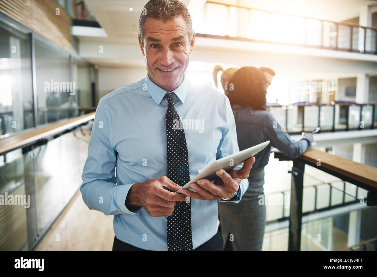 Handsome mature office worker standing with tablet and looking at camera. - Stock Image