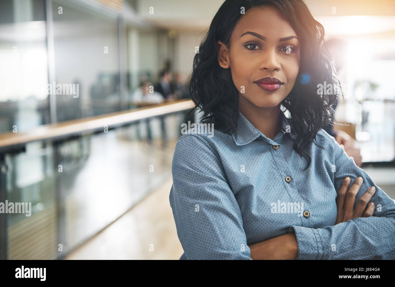 Pretty young dreamy African-American office worker standing with arms crossed and looking at camera. Stock Photo