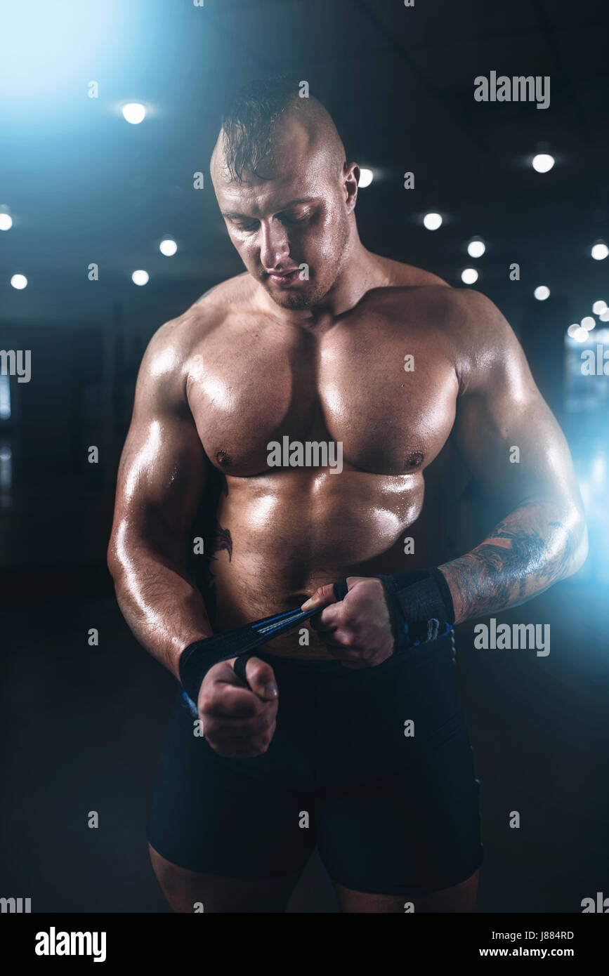 Muscular male athlete posing with dumbbell in sport gym  Fitness