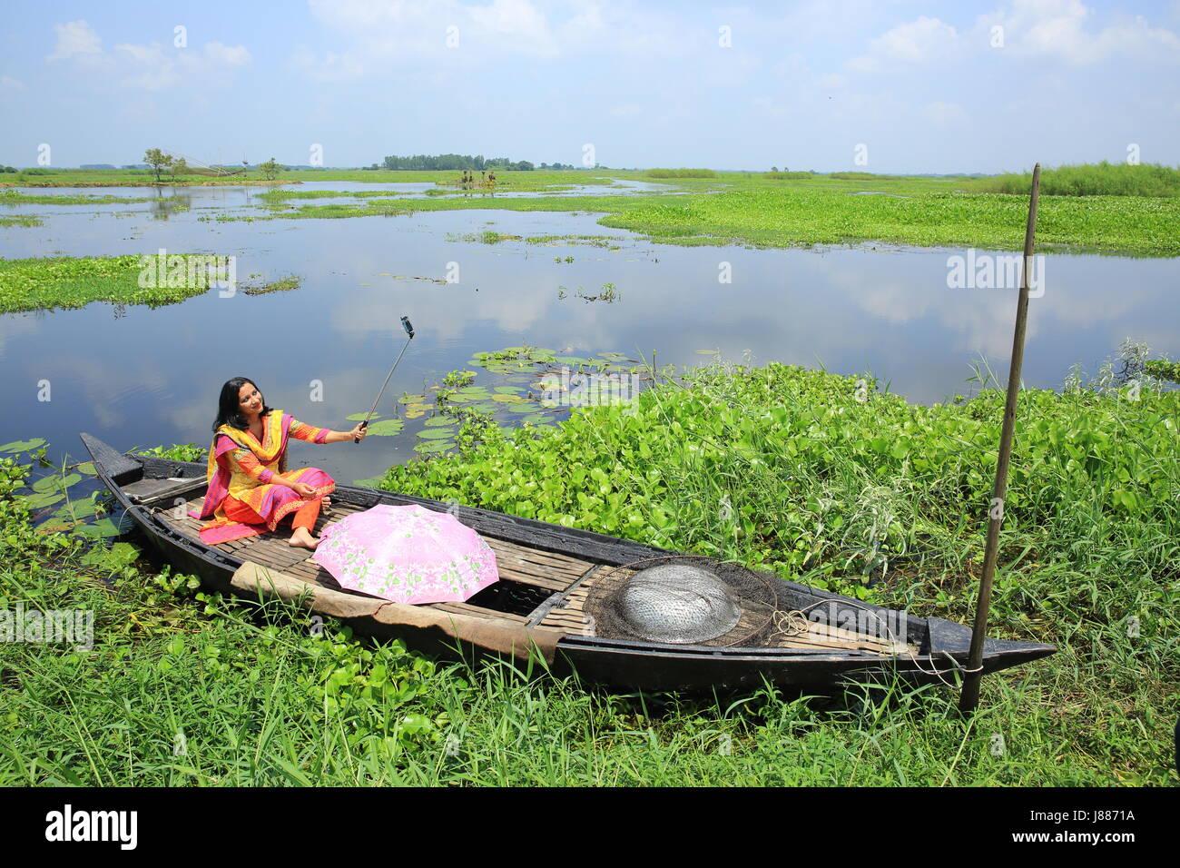 Young woman taking selfie at Arial Beel in Sreenagar, Munshiganj, Bangladesh. - Stock Image