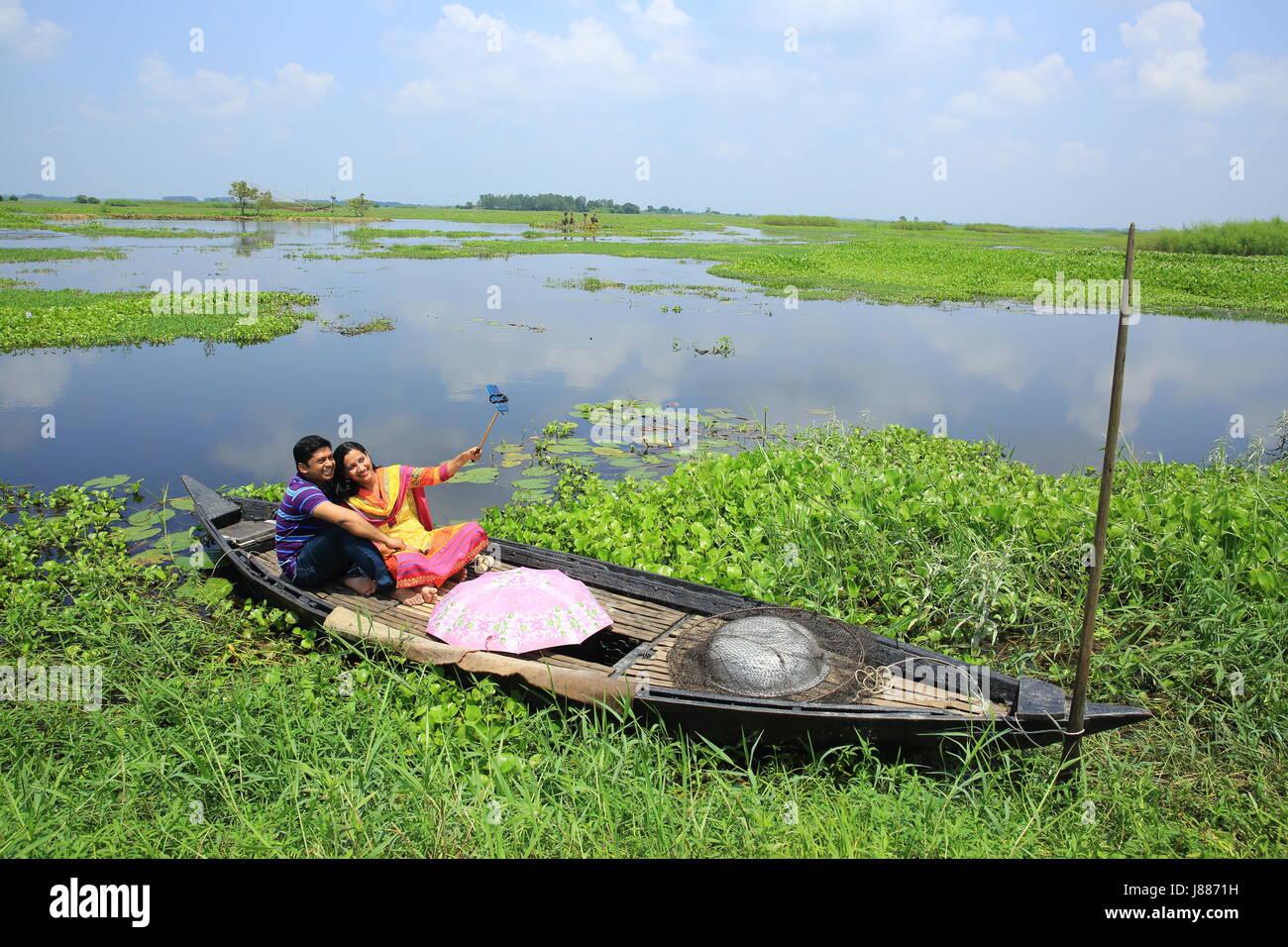 Young couple taking selfie at Arial Beel in Sreenagar, Munshiganj, Bangladesh. - Stock Image