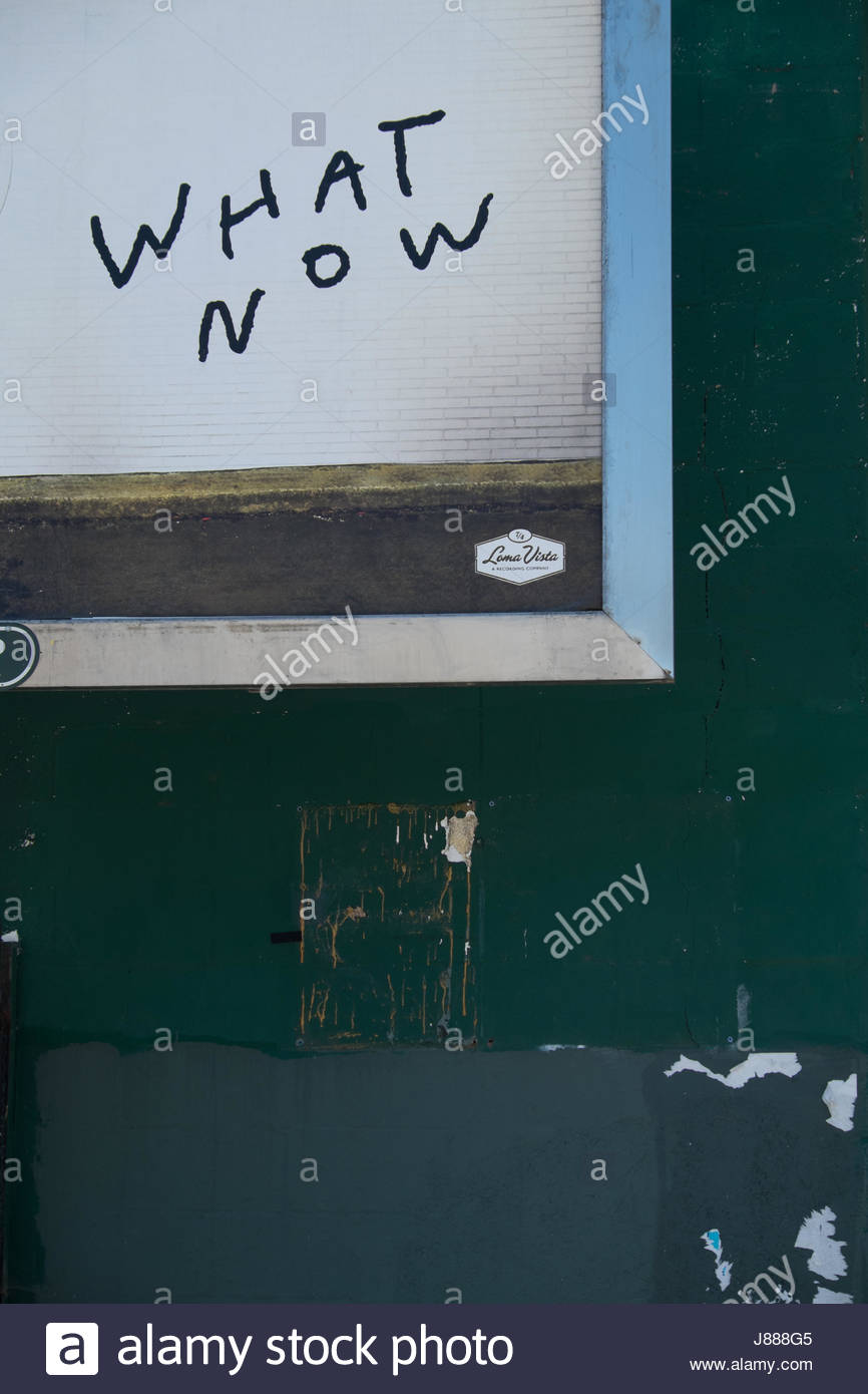 What now sign on a green wall with a yellow square with a question mark in it. - Stock Image