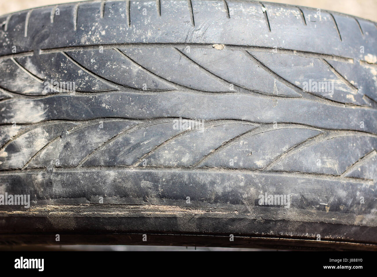 Old worn car tires on a gray background - Stock Image