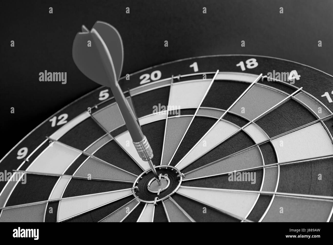 Dart arrow hitting in the target center of dartboard (Black And White) - Stock Image