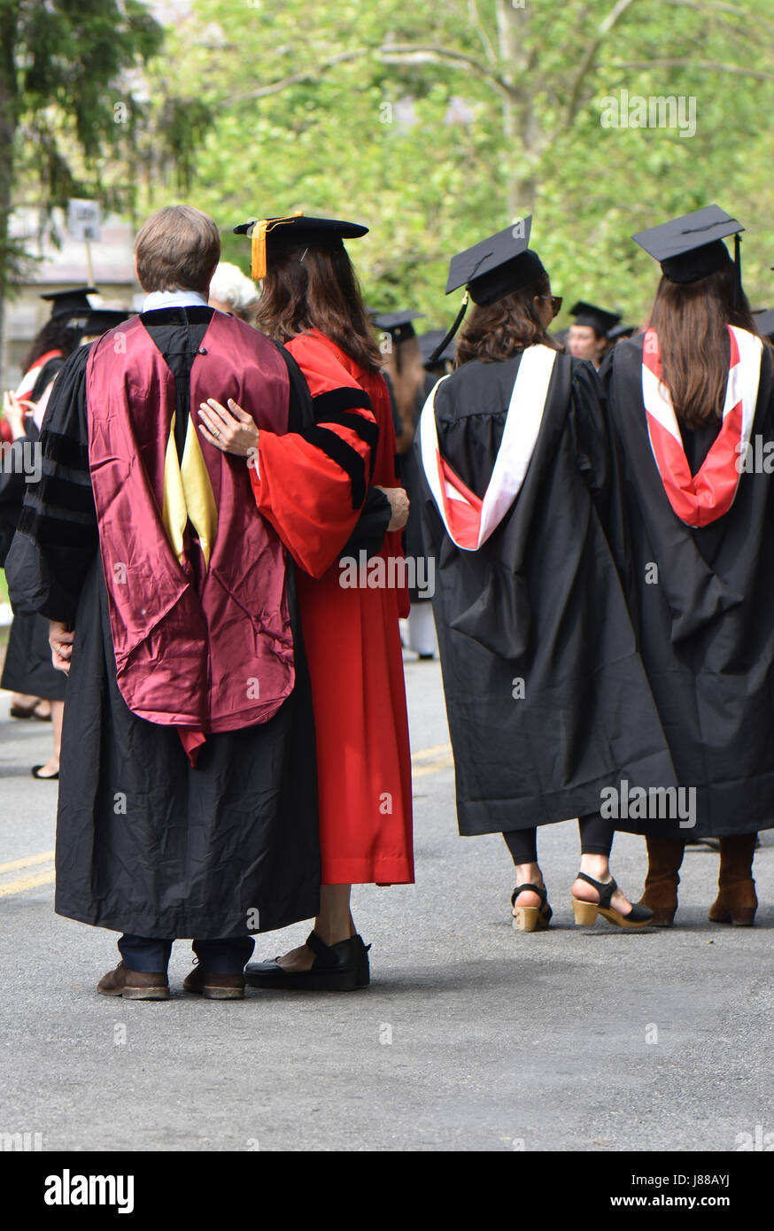 Dressed in graduation robes and caps students and parents celebrate the day. - Stock Image
