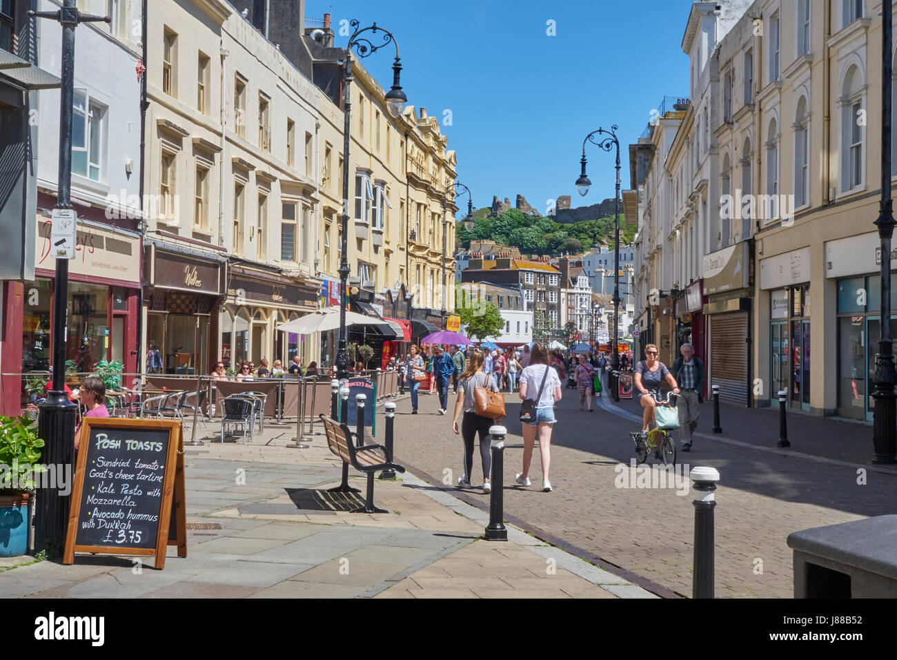 Hastings, the view along the cafes and bars of Robertson Street towards the hill top Norman Castle, East Sussex, Stock Photo