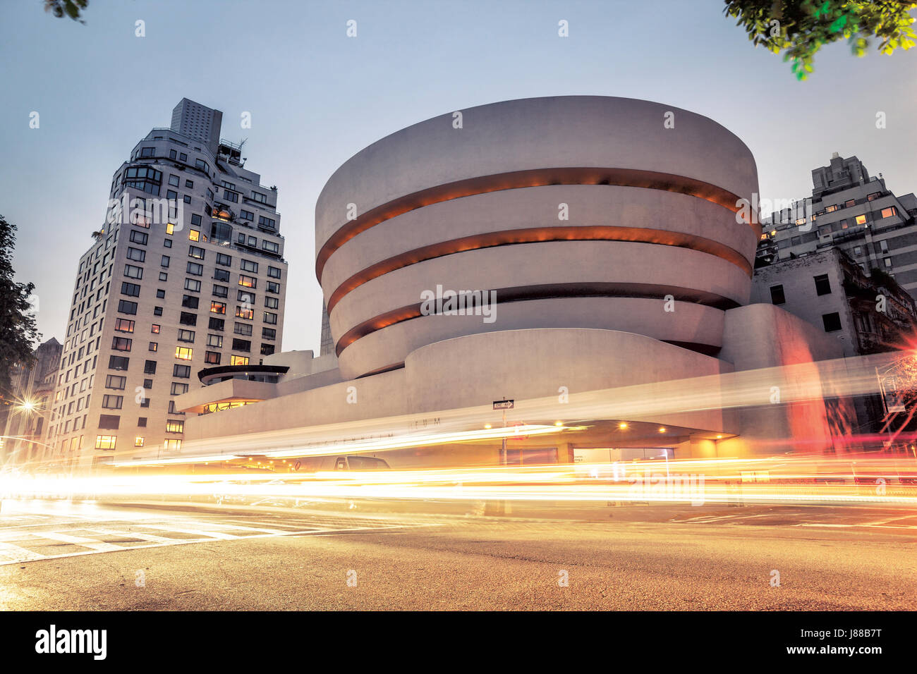 Goggenheim museum at night in New York City with traffic lights in front - Stock Image