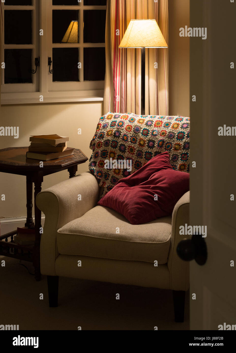cosy armchair at night - Stock Image