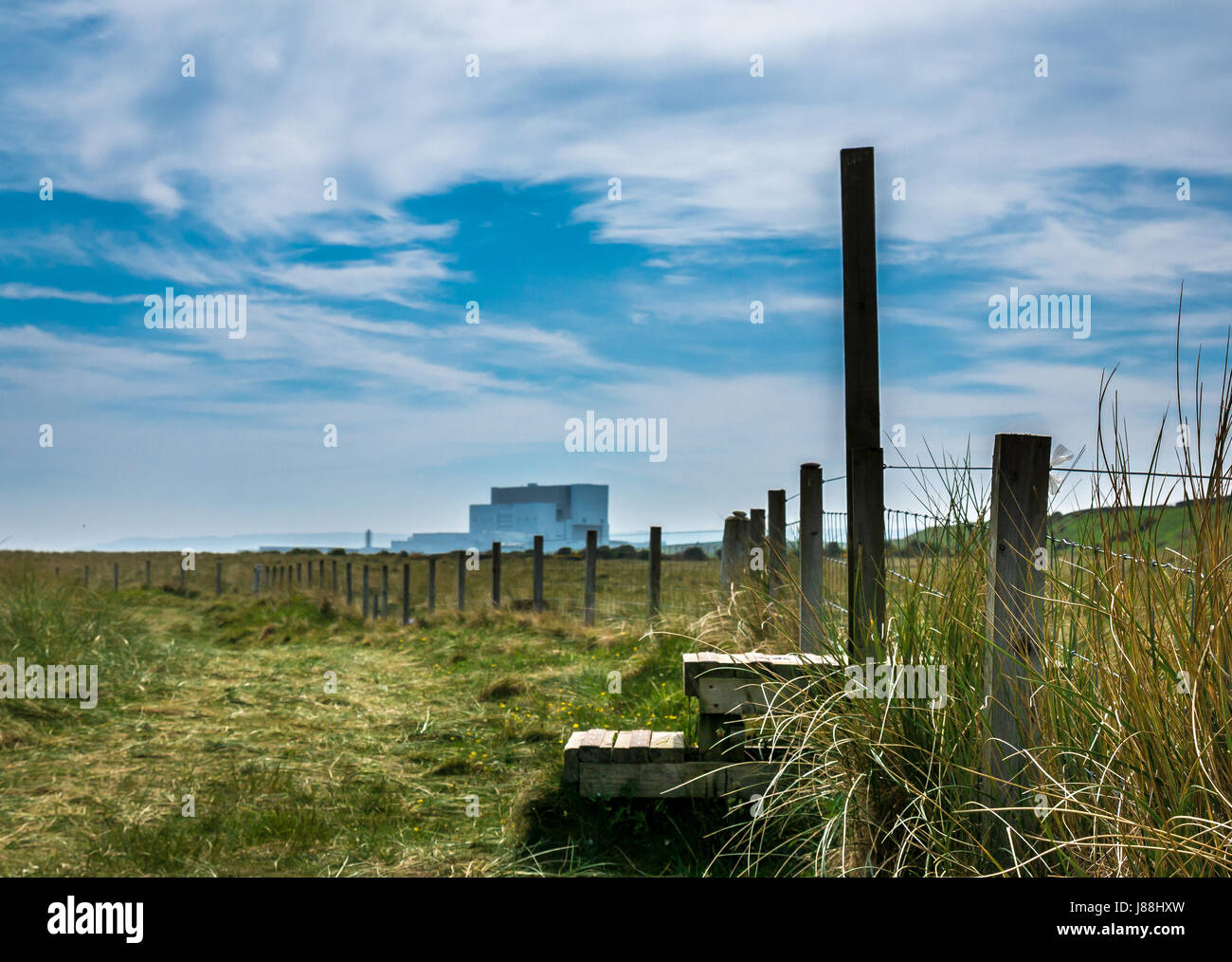 Ground level view along John Muir Way coastal path, with Torness Nuclear Power Station on horizon and stile over - Stock Image