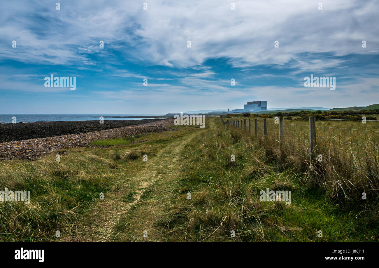 Ground level view along the John Muir Way coastal path fence line with Torness Nuclear Power Station on horizon - Stock Image