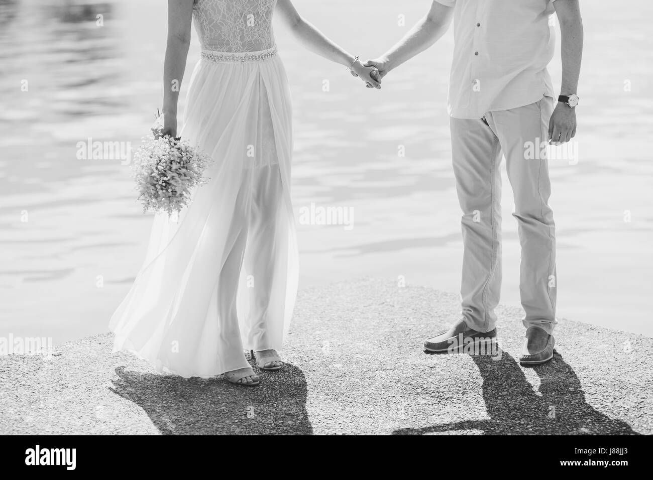 Newlyweds hold hands on the sea. Couple holding hands. Wedding in Montenegro. Stock Photo