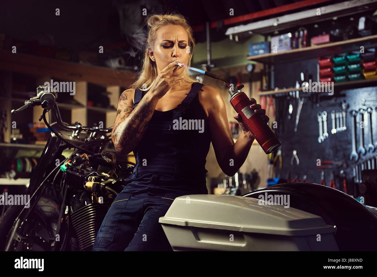 Woman mechanic lights up a cigarette with a gas burner in a motorcycle workshop - Stock Image