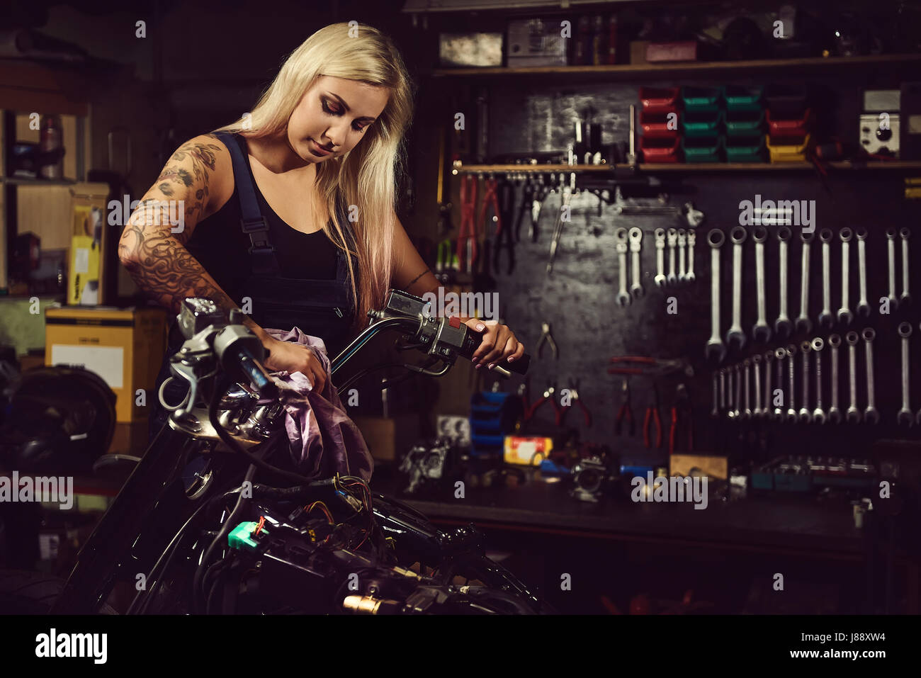 Blond woman mechanic working in a motorcycle workshop - Stock Image