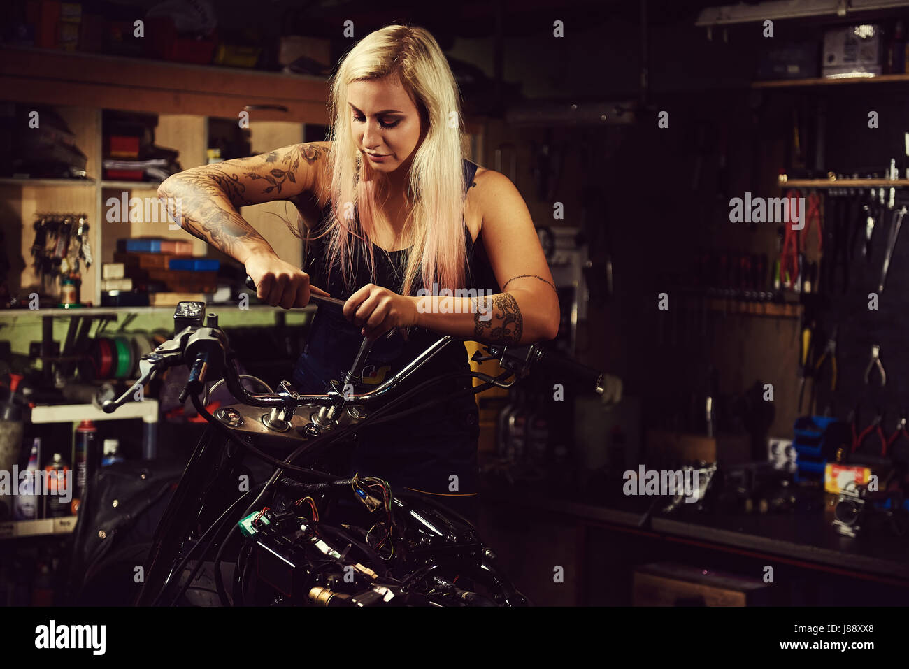 Blond woman mechanic repairing a motorcycle in a workshop - Stock Image