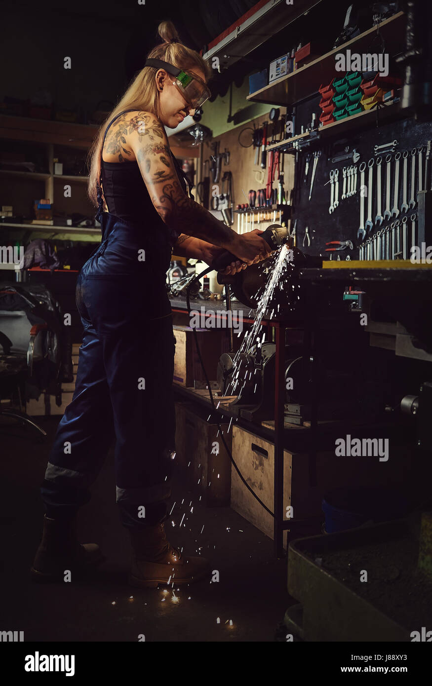 Woman mechanic working in a motorcycle workshop - Stock Image