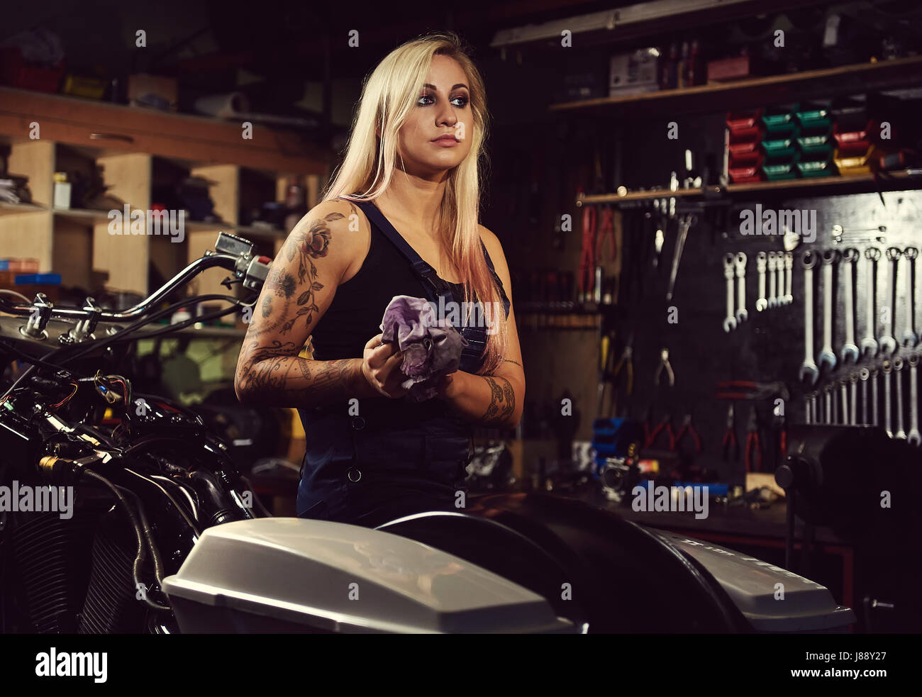Blond woman mechanic in a motorcycle workshop - Stock Image